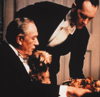 Master and Servant: Richard E Grant, playing the first footman, George, offers something fowl to Michael Gambon, Sir William McCordle.